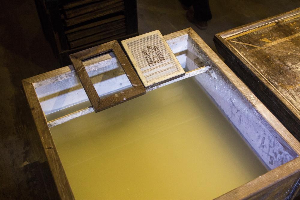 Рамка для изготовления бумаги, лежащая на ёмкости с бумажной пульпой