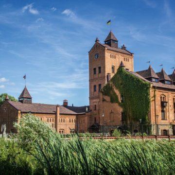 Вид на «Замок-музей Радомысль» со стороны озера. На переднем плане корпус, в котором расположены концертный зал (цокольный этаж), обрядовый зал (1 этаж), отель «Via Regia» (2 этаж) и гетманские апартаменты (мансарда)