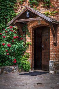 Стены замка у входа в концертный зал и трапезную «Via Regia» украшают английские плетистые розы