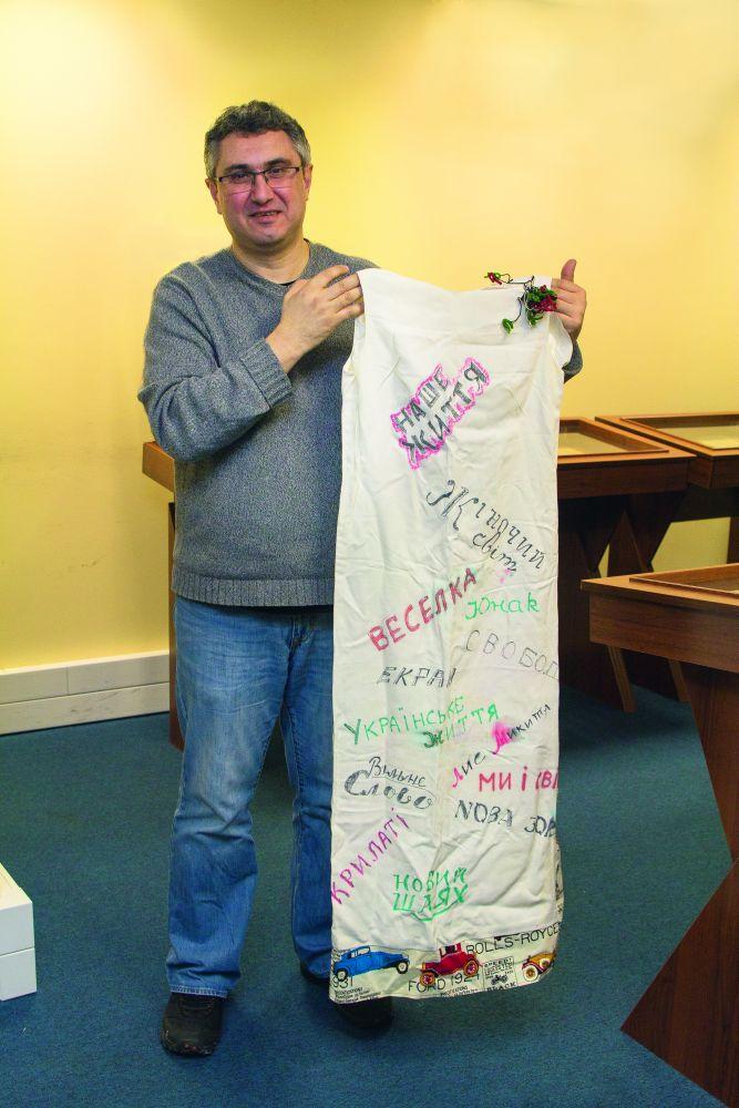 В руках у коллекционера уникальное платье — память о «Бале прессы», состоявшемся в 1960-х гг. в Чикаго. Надписи — названия украинских газет и журналов, выходивших тогда за океаном