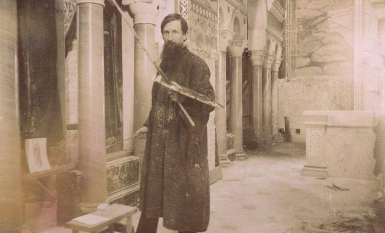 Виктор Васнецов поправляет вставленные в рамы иконы главного иконостаса. Фото 1893 г.