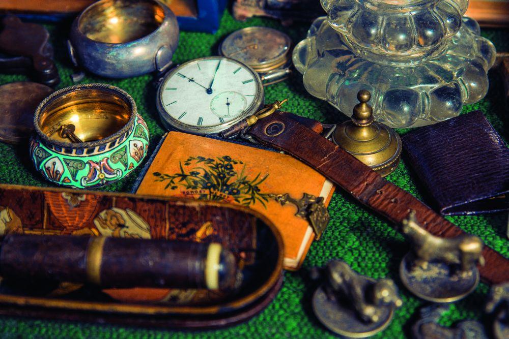 Фрагмент домашнего музейчика: серебряная солонка сэмалевым узором, наручные часы сключиком длязаводки, записная книжка сотрывными листками икарандашиком вспециальном кармашке