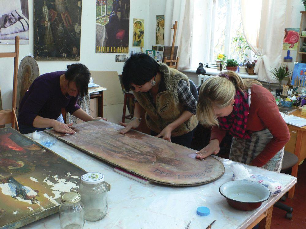 Реставраторы станковой живописи М.Грига, О.Лисаневич иН.Дудник работают надиконой сфасада Трапезной церкви